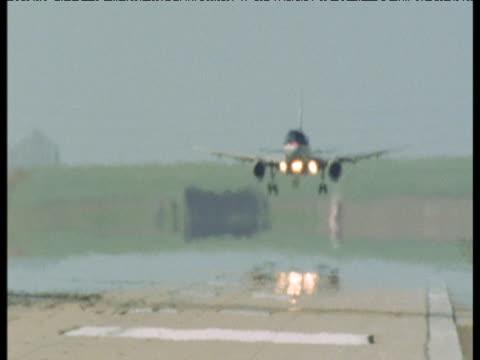stockvideo's en b-roll-footage met passenger jet lands on runway in thick heat haze, denver airport - dia