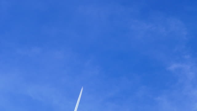 passenger jet plane with contrail against blue cloudly sky - vapour trail stock videos & royalty-free footage