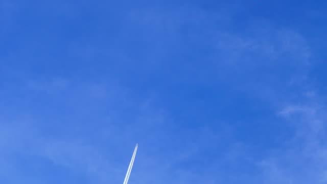 vídeos y material grabado en eventos de stock de passenger jet plane with contrail against blue cloudly sky - vapor