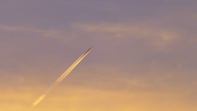 passenger jet plane with contrail against dusk sky - sky only stock videos & royalty-free footage