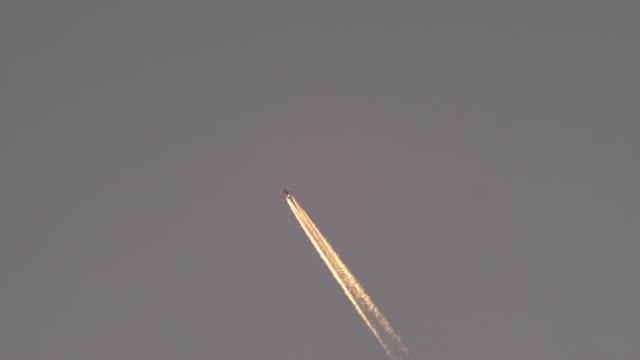 Passenger jet plane with sunlit contrail against clear dusk sky