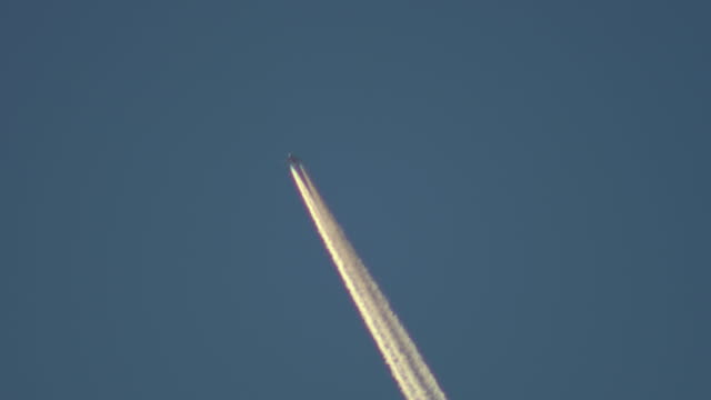 Passenger jet plane with thick white contrail against clear blue sky