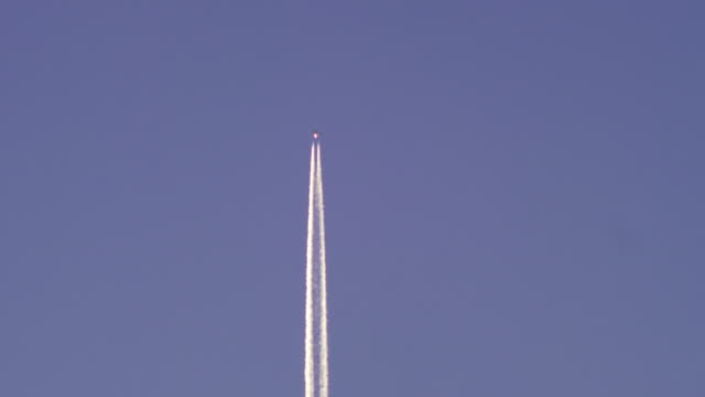 Passenger jet plane with white contrail against clear blue sky