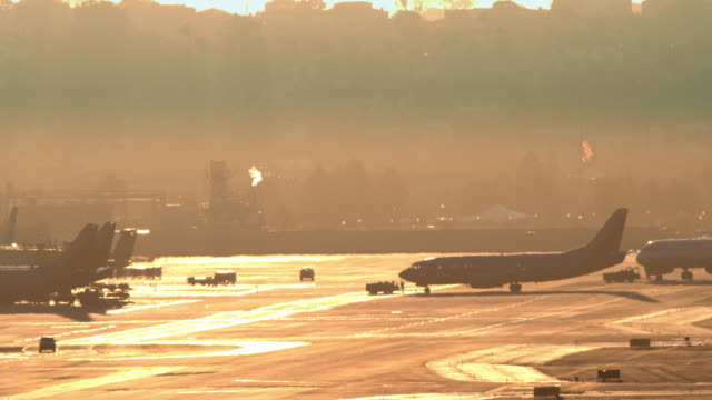 ws passenger jet pushed across airport tarmac near terminal in silhouette shadow against late afternoon sun light / san diego, california, usa  - asphalt stock videos and b-roll footage