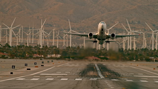 ls passenger jet take-off from airport runway fills air with hot fumes from jet engines against background of spinning turbines of wind farm - palm springs california stock videos & royalty-free footage
