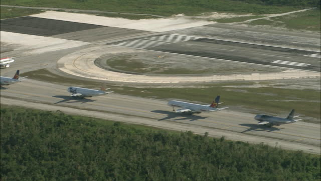 aerial passenger jets lined up on taxiway of airport / cancun, quintana roo, mexico - taxiway stock-videos und b-roll-filmmaterial