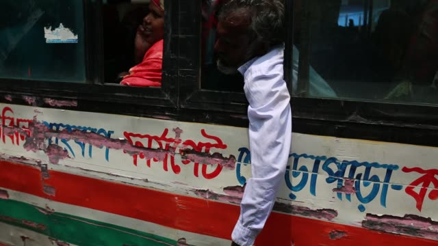 vidéos et rushes de a passenger keep his hand outside a running bus in a busy street in dhaka bangladesh on april 19 2018 at least 4284 people including 516 women and... - population explosion
