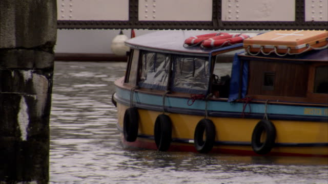 A passenger moves inside a small ferry as it cruises on a river. Available in HD.