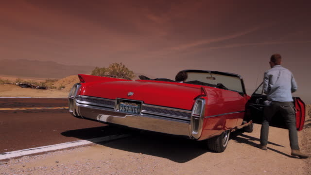 a passenger of a red vintage convertible relieves himself by the side of the road, then gets back in and the driver pulls onto the highway. - collector's car stock videos and b-roll footage