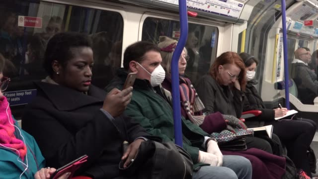 passenger on the london underground wears a surgical mask during the coronavirus pandemic in london on march 6, 2020 in london, england. - protective face mask stock videos & royalty-free footage