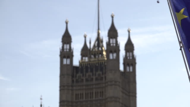 a passenger plane flies past victoria tower while proeurope protestors gather opposite parliament with european union flags as members of the... - victoria tower stock videos & royalty-free footage