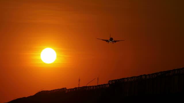 Passenger plane landing on airport runway during sunset