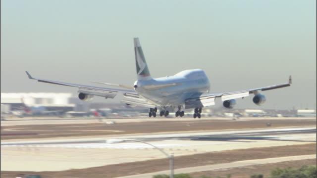 stockvideo's en b-roll-footage met ws pan passenger plane landing on runway at lax airport / los angeles, california, usa - lax airport