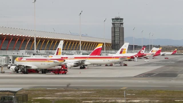 A passenger plane operated by Iberia airlines a unit of International Consolidated Airlines Group SA sits on the tarmac as the control tower stands...