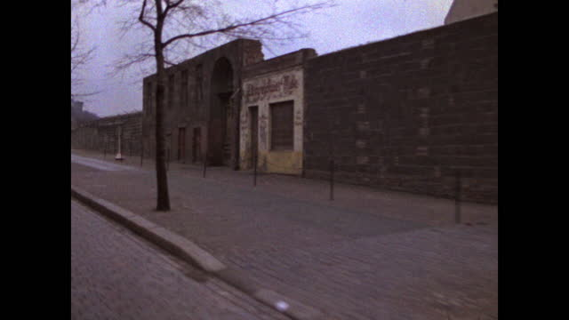 passenger point of view driving along the berlin wall and past closed shop fronts in berlin; 1969. - establishing shot stock videos & royalty-free footage