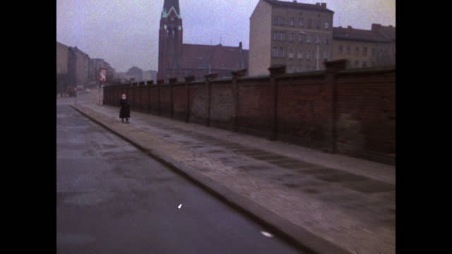 passenger point of view driving along the berlin wall past parked cars in berlin; 1969. - national landmark stock videos & royalty-free footage