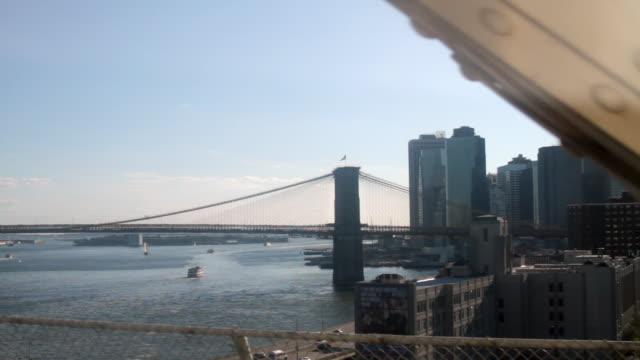 Passenger point of view of Manhattan and the Brooklyn Bridge from the N Train window on the Manhattan Bridge.