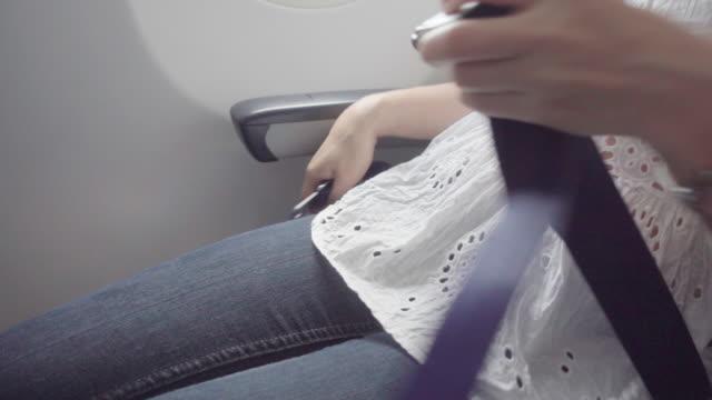 stockvideo's en b-roll-footage met passagier voorbereiden om te vergrendelen vliegtuig dragen van de veiligheidsgordel - veiligheidsgordel