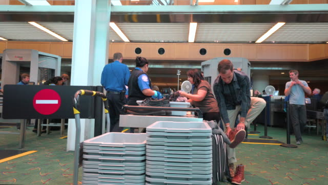 Passenger putting on shoes after clearing TSA security checkpoint at Portland International Airport