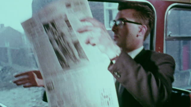 vídeos de stock e filmes b-roll de 1967 ms passenger reading newspaper on bus / handsworth, west midlands, england - jornal