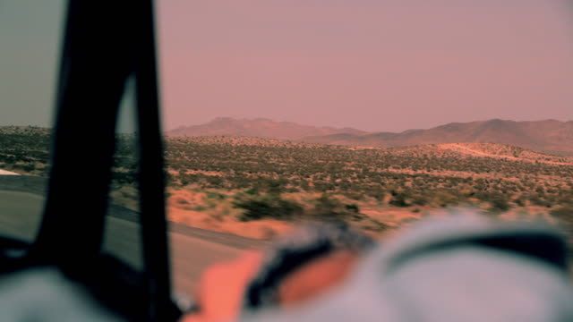 a passenger rides in a convertible traveling through a desert. - convertible stock videos & royalty-free footage