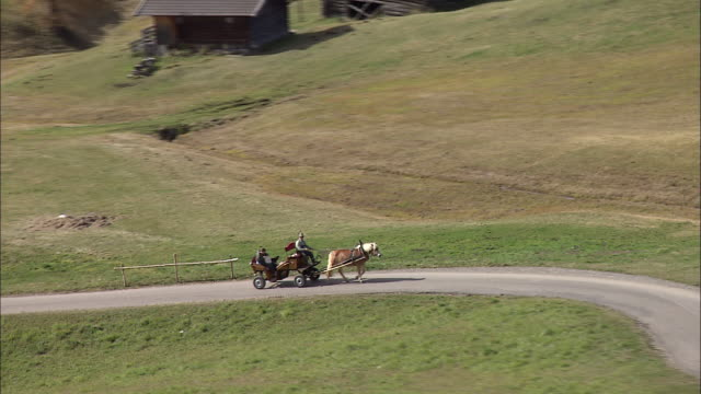 vidéos et rushes de a passenger rides in a horse-drawn carriage through the hilly countryside. - wagon