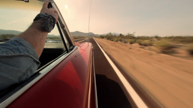 A passenger rides in a vintage red convertible traveling on a desert highway.