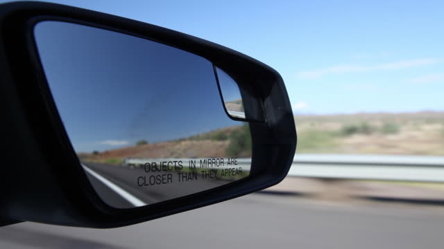 passenger pov shot from a car showing a wing mirror reading 'objects in mirror are closer than they appear', arizona, usa. - wing mirror stock videos & royalty-free footage