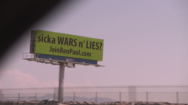 Passenger POV shot from a highway showing a billboard saying 'sicka WARS n' LIES' promoting politician Ron Paul USA FKAX251A Clip taken from...