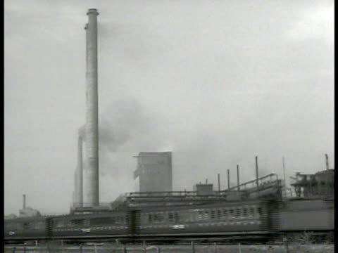 passenger steam train passing factory building smoke stack. electric train passing on railroad tracks. - steam train stock videos & royalty-free footage