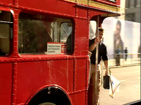 Passenger steps off back of double decker bus