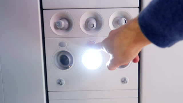 Passenger Switches Off Reading Lamp in Airplane Overhead Panel - Stock Video