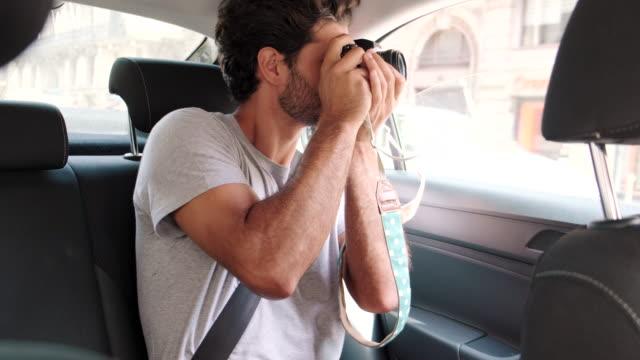 vídeos de stock, filmes e b-roll de passageiro tirando foto com câmera do banco de trás do carro - passenger
