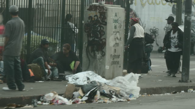 Passenger POV of tents and individuals on sidewalk in Skid Row