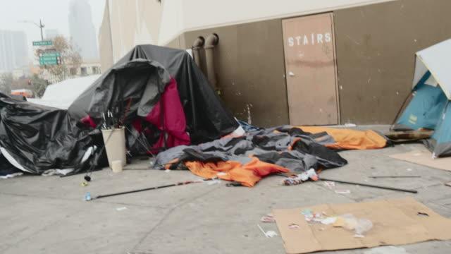 vídeos de stock, filmes e b-roll de passenger pov of tents and individuals on sidewalk in skid row - gueto