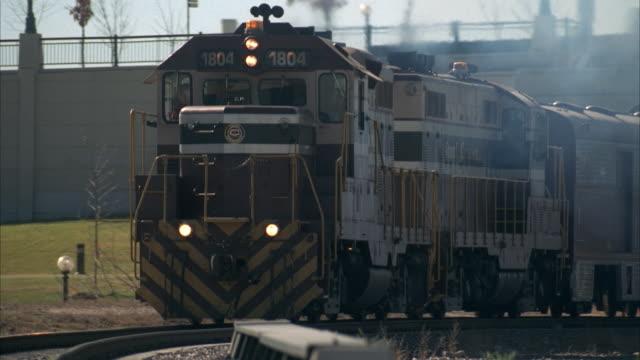 vídeos de stock e filmes b-roll de ms, pan passenger train and freight train riding on railroad yard - rasto de movimento