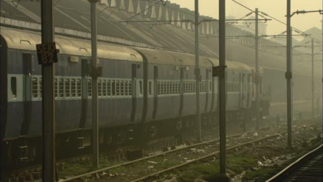 vídeos de stock e filmes b-roll de ms pan cu passenger train arriving at station under hazy sky / india - rasto de movimento