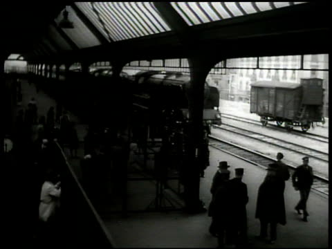 passenger train arriving in crowded railroad station platform. int british foreign secretary robert a. eden walking in hallway corridor w/ men. london - 1935 stock-videos und b-roll-filmmaterial