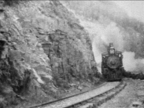 B/W 1898 passenger train coming around bend by mountain / newsreel