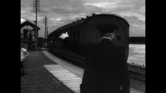 vidéos et rushes de montage passenger train coming to a stop and waiting for a postal special train to pass / united kingdom - 1936
