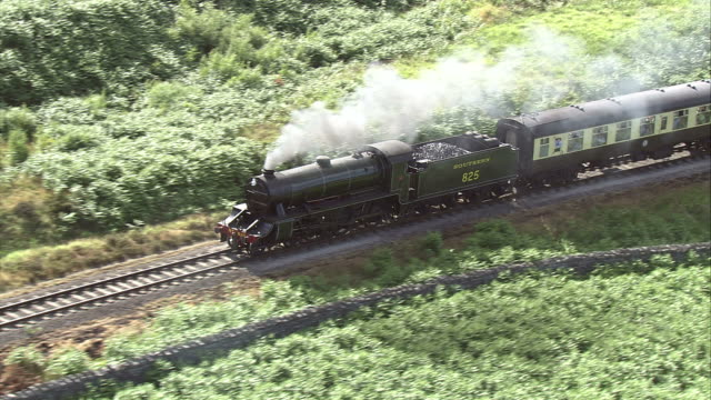 A passenger train crosses through the Scottish countryside. Available in HD.