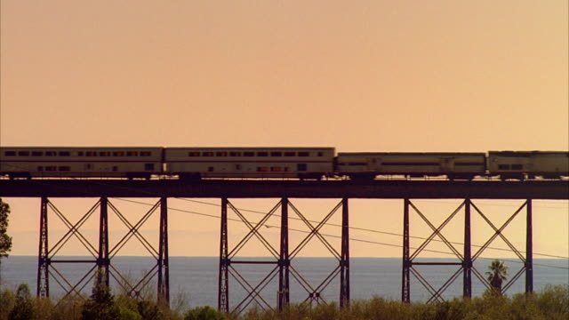 ws passenger train crossing trestle at sunset, santa barbara, california, usa - ponte video stock e b–roll