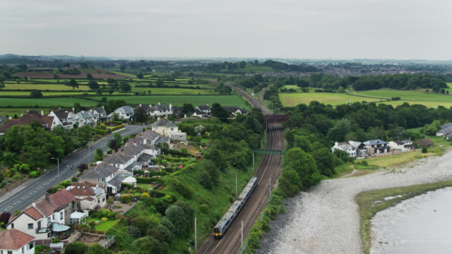passenger train in lancashire countryside - drone shot - estuary stock videos & royalty-free footage