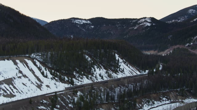 stockvideo's en b-roll-footage met passagierstrein in snowy pass in montana-drone shot - locomotief
