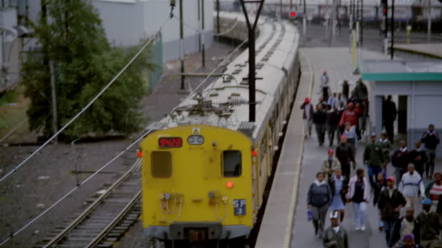 passenger train leaving railway station / commuters walking on railway station platform / paarden eiland / cape town, south africa - 2006 stock videos & royalty-free footage