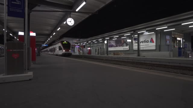 passenger train leaving station at night - station stock-videos und b-roll-filmmaterial