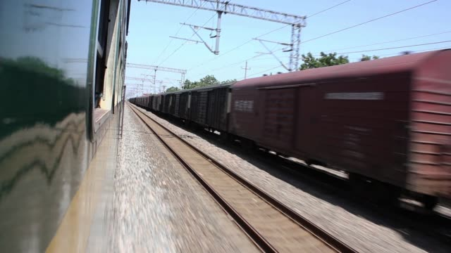 a passenger train moves past a stationary freight train. - c119gs stock videos & royalty-free footage