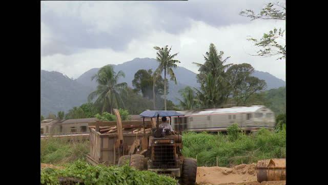passenger train passes through rural malaysia landscape; 1996 - 1996 stock videos & royalty-free footage