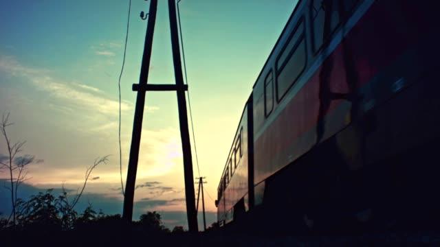 personenzug vorbei bei sonnenuntergang - lokomotive stock-videos und b-roll-filmmaterial
