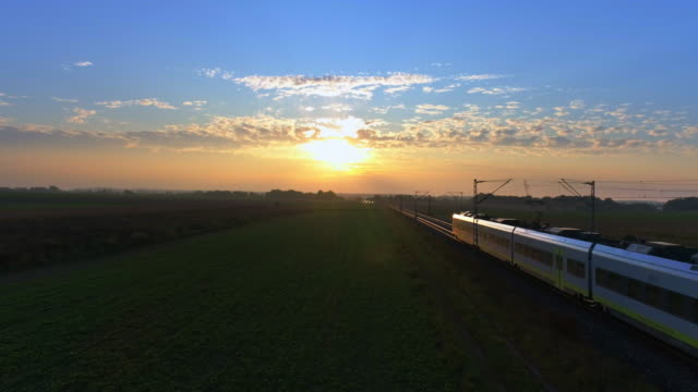 stockvideo's en b-roll-footage met passagierstrein passeren platteland bij zonsondergang - train vehicle